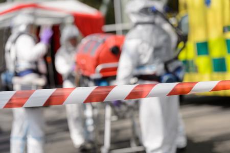 hazardous material team: Closeup of crossing barrier tape biohazard medical team in background Stock Photo