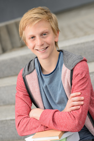 Smiling teenage student boy with books sitting outside on steps photo