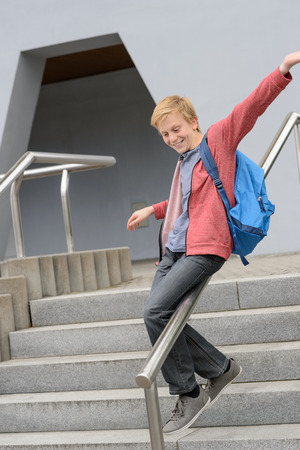 Excited teenage student sliding down handrail on school stairway photo