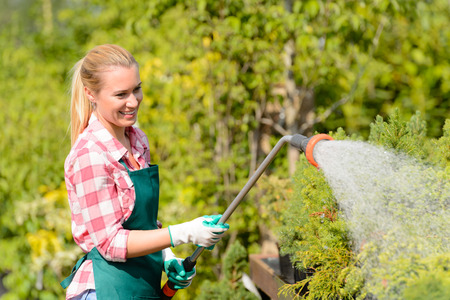 Garden center woman worker watering plants with hose smiling sunny photo