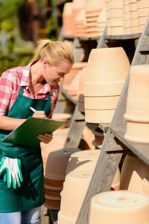 ollas de barro: Mujer del centro de Garden notas trabajador escritura de arcilla ollas estante Foto de archivo