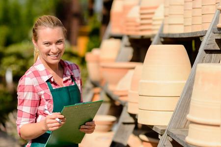 garden center: Garden center woman worker standing by clay pots shelf smiling Stock Photo
