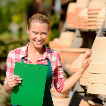 ollas de barro: Centro de jardiner�a, trabajador, mujer de pie junto a las ollas de arcilla estante sonriendo