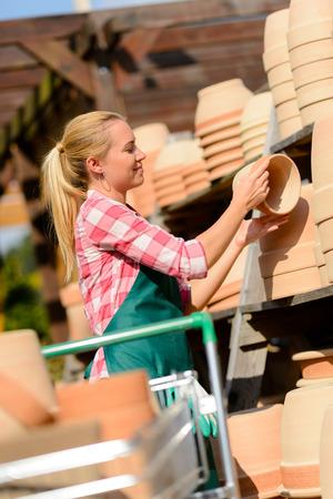 ollas de barro: Trabajador de centro de la mujer del jard�n con macetas de arcilla en la cesta de compras Foto de archivo