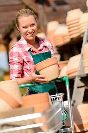ollas de barro: Jardines trabajadora poniendo ollas de barro en la cesta de compras