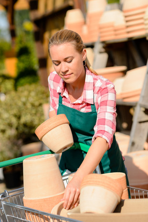 refilling: Garden center woman worker putting clay pots on shopping cart Stock Photo