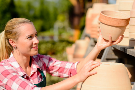 ollas de barro: Jardines trabajadora poniendo ollas de barro en el estante soleado