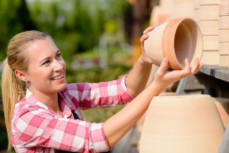 garden center: Garden center woman worker putting clay pots on shelf smiling