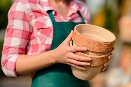ollas de barro: Dos ollas de barro en manos de jard�n trabajador del centro de primer plano soleado