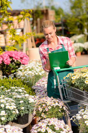 Garden center woman worker checking flowers writing inventory notes sunny photo