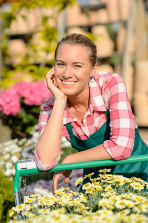 garden center: Garden center smiling woman worker leaning against shopping cart sunny