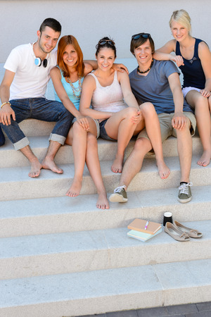 Full length of happy college students sitting together on campus  stairs photo