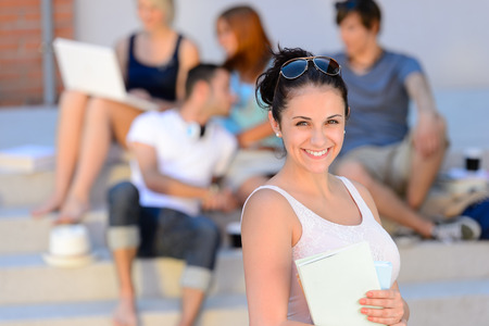 beautiful boys: Summer college student girl smiling holding books friends in background