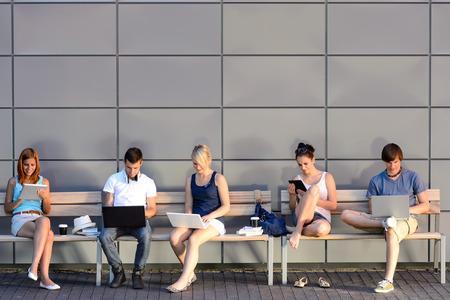 colegios: Estudiantes universitarios internet adicci�n a la computadora sentado banco fuera de campus de verano Foto de archivo