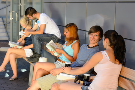 Group of students with books hanging out sitting outside campus photo