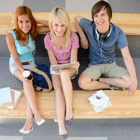 Top view of three college students looking at camera sitting photo