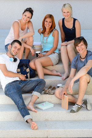 College students sitting on school stairs during break summer relaxing photo