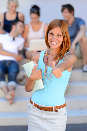 Smiling college student girl thumb-up friends in background summer time photo