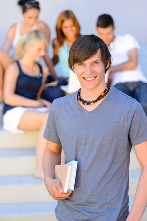 Smiling college student boy holding books friends in background summer photo