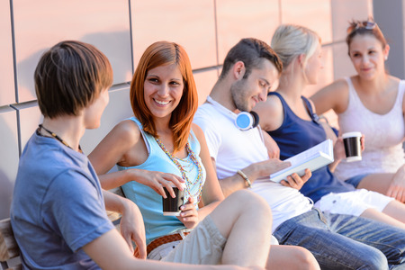 College students sitting in row modern wall outside summer campus photo