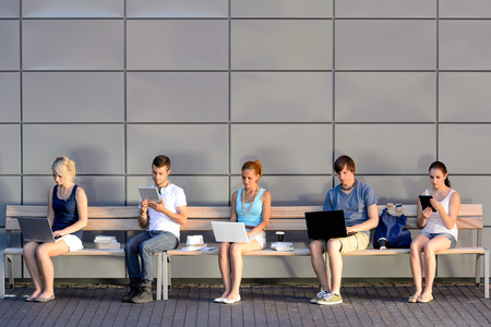 Les étudiants de la dépendance des médias sociaux en utilisant un ordinateur portable assis dans la rangée Banque d'images