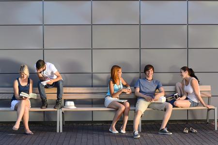 大学生のキャンパスの外の現代の壁でベンチに座っています。