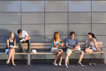 College students sitting on bench by modern wall outside campus photo