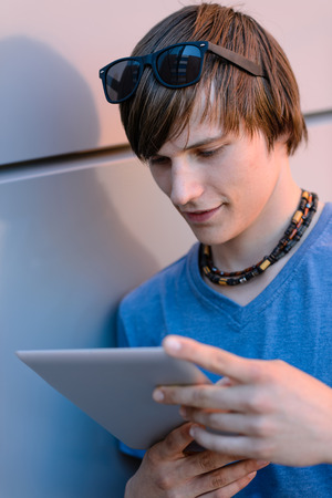Student boy looking at tablet leaning against wall photo