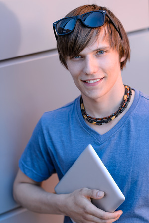 Happy student boy with tablet looking at camera against wall photo