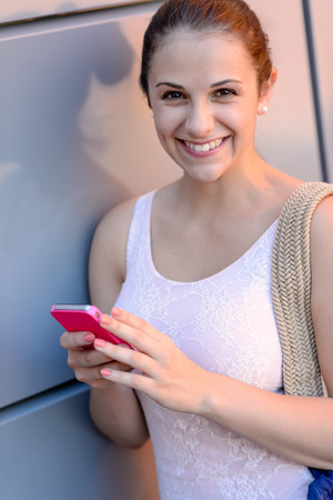 Smiling student girl with mobile phone leaning against modern wall photo