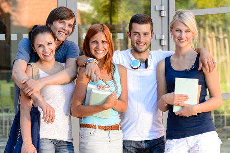Group of smiling students standing front of college campus summer photo