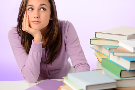 Student girl looking aside sitting behind stack of books purple photo