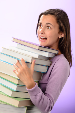 Shocked student girl carry stack of books on purple background photo