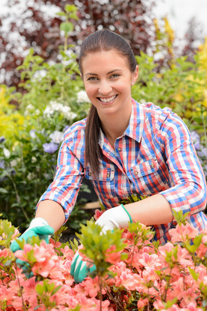 Smiling florist arranging flowers in garden center greenhouse store photo