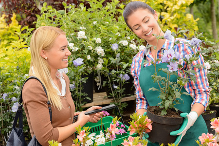 Garden centre woman worker selling potted plant to female customer photo