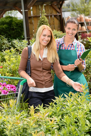 Garden center worker and woman customer shopping for plants smiling photo