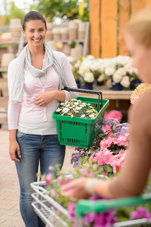 Smiling woman buying flowers carry shopping basket garden center photo