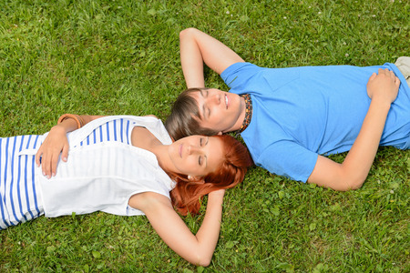 Teenage couple lying on grass relaxing closed eyes top view photo