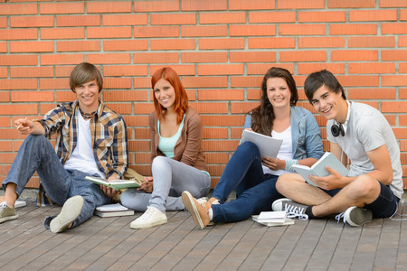 sitting on ground: College students with books sitting ground by brick wall