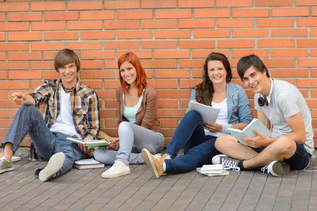 assis par terre: Les �tudiants du Coll�ge avec des livres assis sol par mur de briques