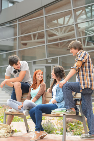 Students friends sitting bench in front of university hanging out photo