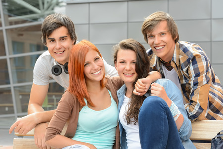 Cheerful group of student friends hugging together outside college photo