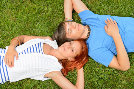 lying on grass: Young couple lying on grass closed eyes enjoy summertime top-view