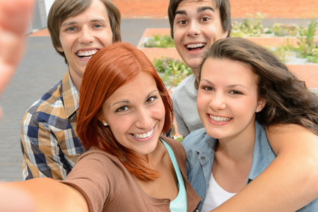 Group of student teenage friends taking selfie laughing at camera photo