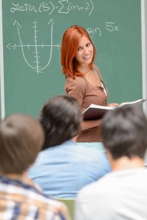 Student girl standing front of green chalkboard looking at classmates photo