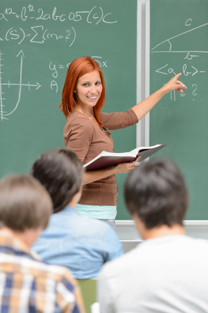 Mathematics student girl pointing on chalkboard looking at classmates photo