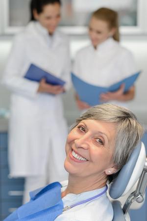 Ltere Frau, die Patienten mit Zahnarzt-Team bei der zahnärztlichen Chirurgie lächelnd Standard-Bild - 29952326