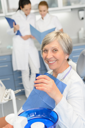 Elderly woman patient dentist team sitting chair at dental surgery Stock Photo - 29952328