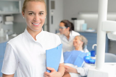 Dental assistant woman smiling at stomatology office dentist with patient