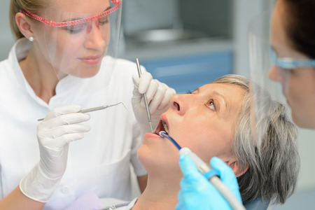 Dental team teeth checkup elderly patient woman open mouth surgery photo